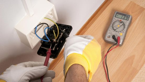 An electrician testing a socket to find an issue