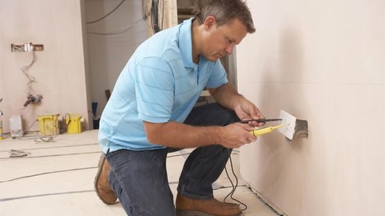 An electrician fully re-wiring a room